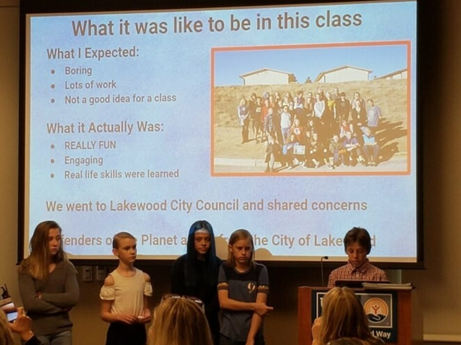"""Students stand at a podium in front a presentation titled """"What it was like to be in this class"""""""