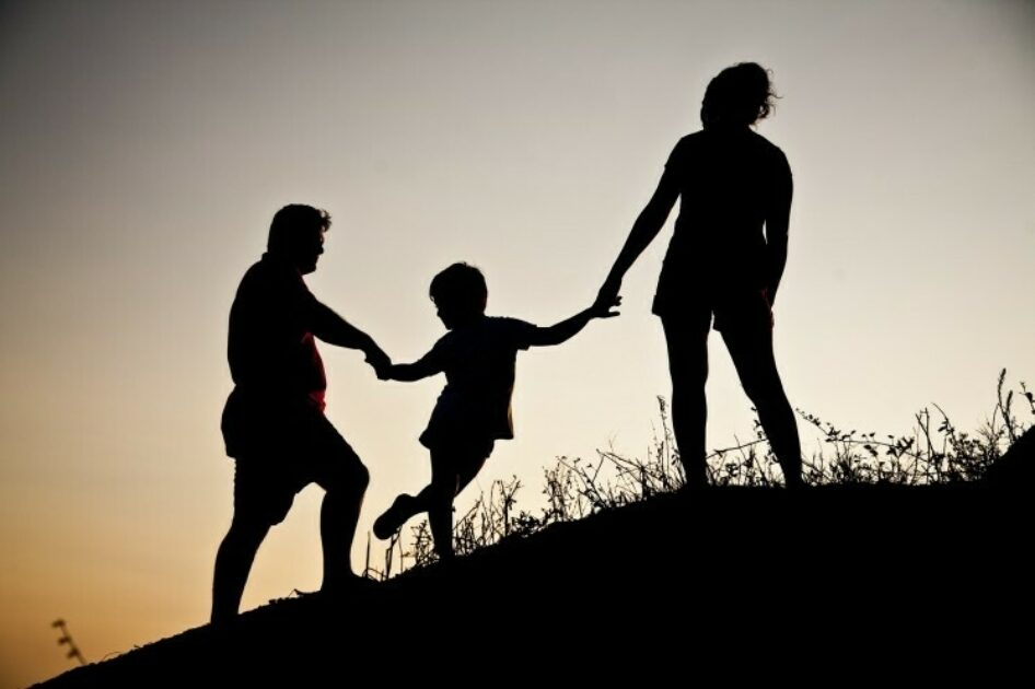 Silhouette of family climbing a hill.