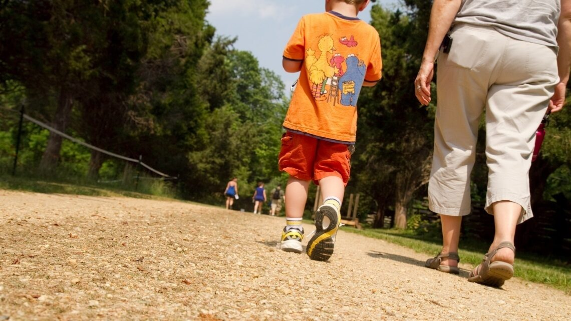 Child and adult walking along a path
