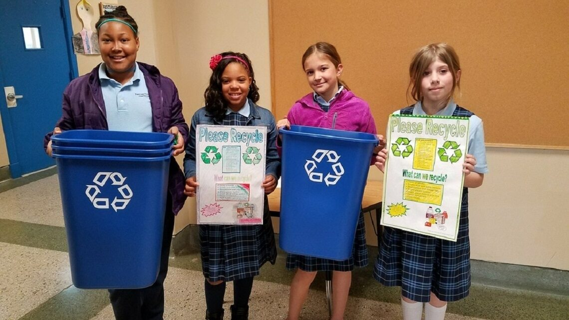 Students holding up recycle bins and posters