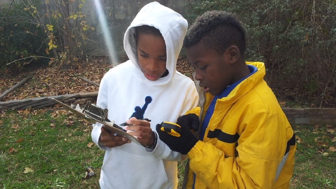 Two young students taking notes on a pad while reading a water quality meter.