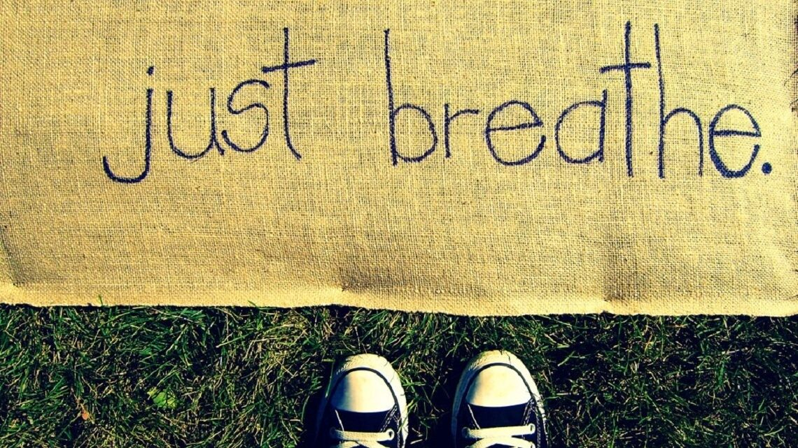 """Child standing in front of a mat saying """"just breath"""""""