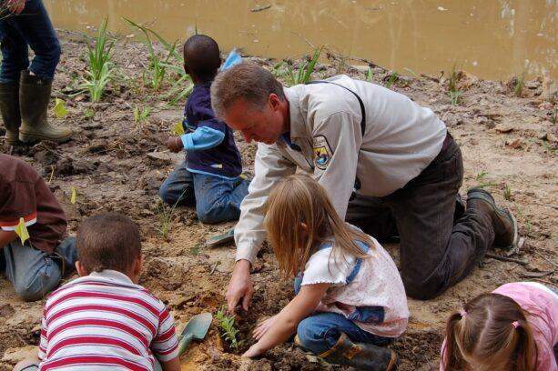 Biologist Rich Mason helps students plant a schoolyard wetland.
