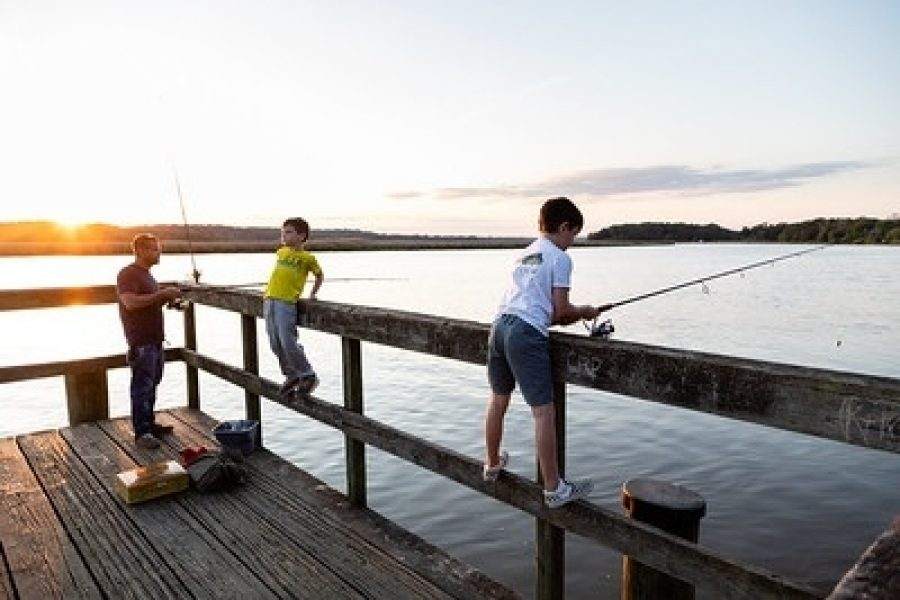 A man and two boys fishing off pier at public access site