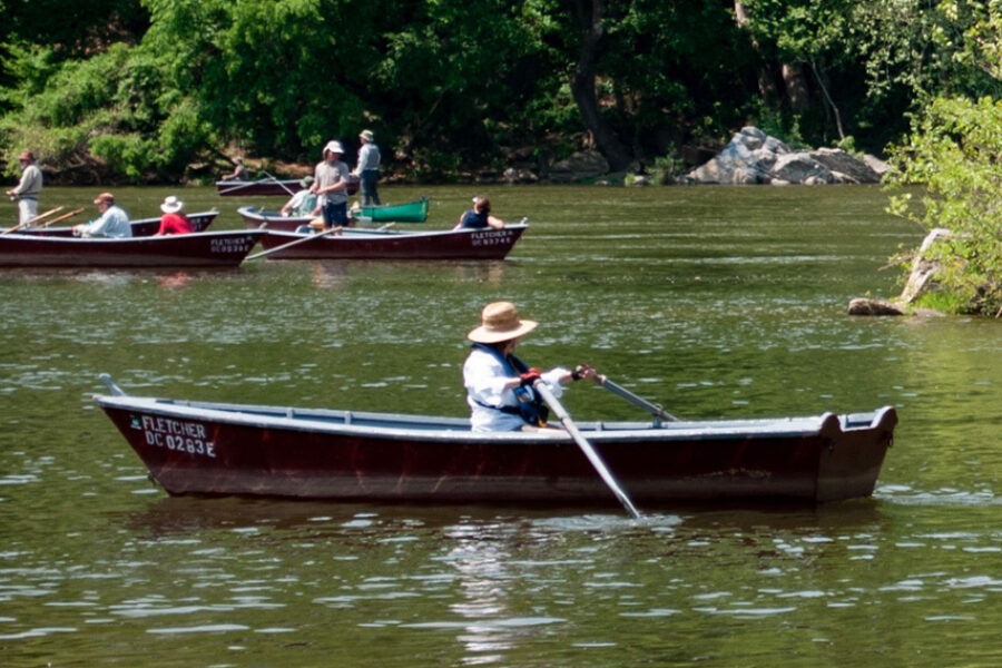 Group canoeing on a wide river.
